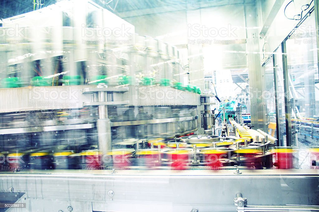 Cans of drink speed through a facility stock photo