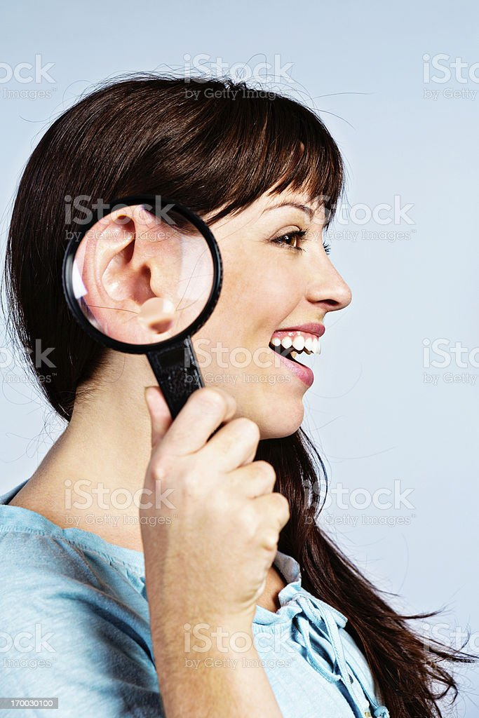 I can't hear you! Magnifying glass enlarges smiling woman's ear stock photo
