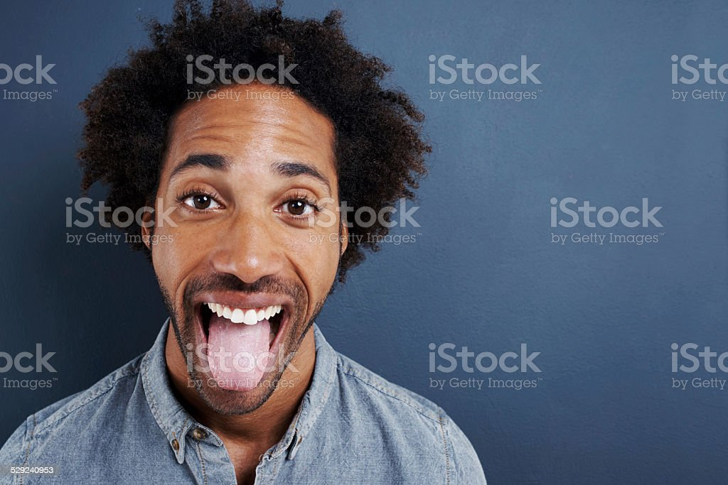 Portrait of a happy young man sticking his tongue out on a gray...