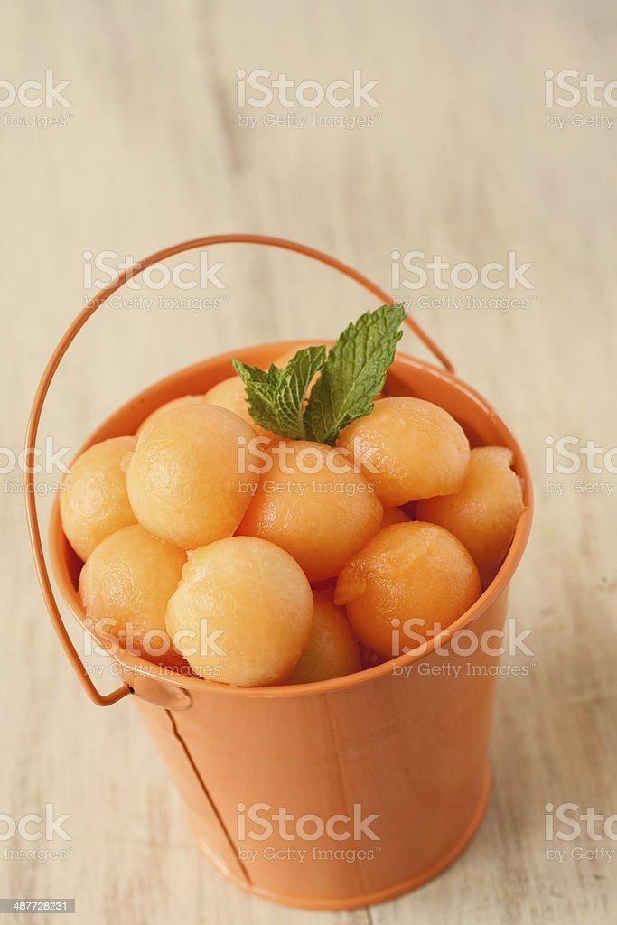 Cantaloupe Balls In Orange Bucket stock photo