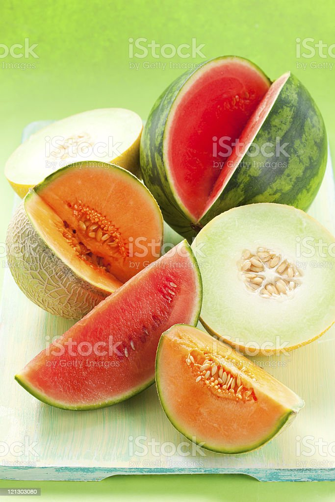 Cantaloupe, melon and watermelon on a green cutting board stock photo