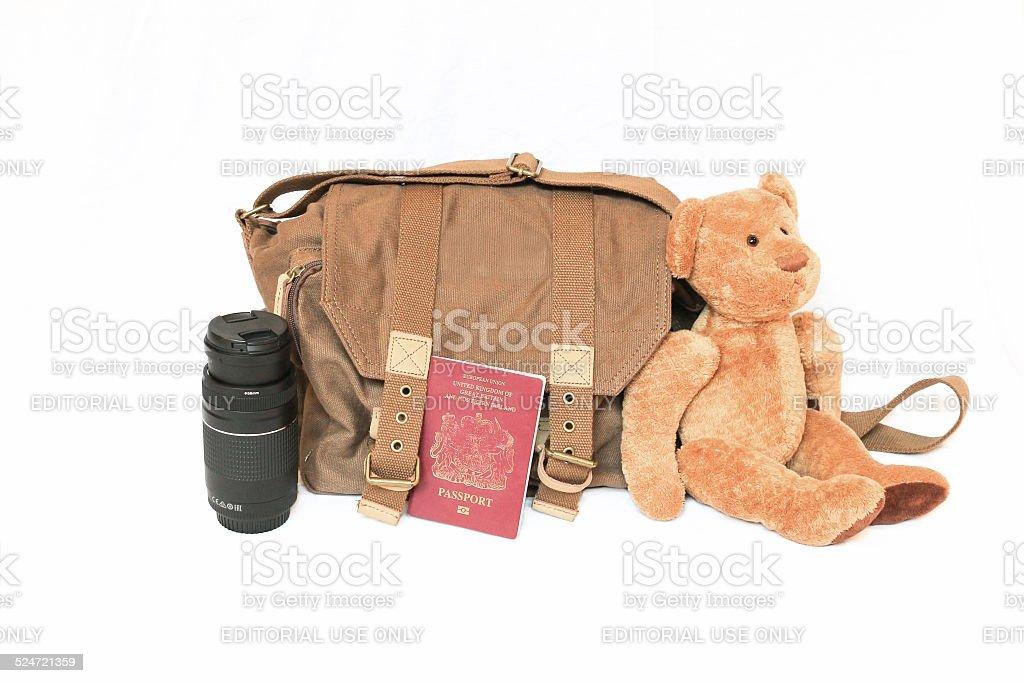 Canvas bag, British passport, zoom lens and teddy bear. stock photo