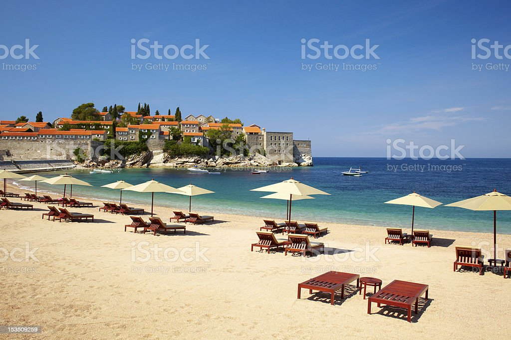 Canvas chairs and parasols on the beach stock photo
