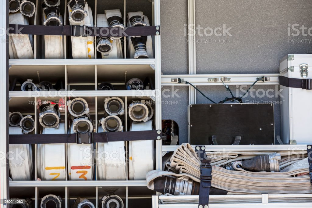 canvas hoses folded up in side of a fire truck stock photo