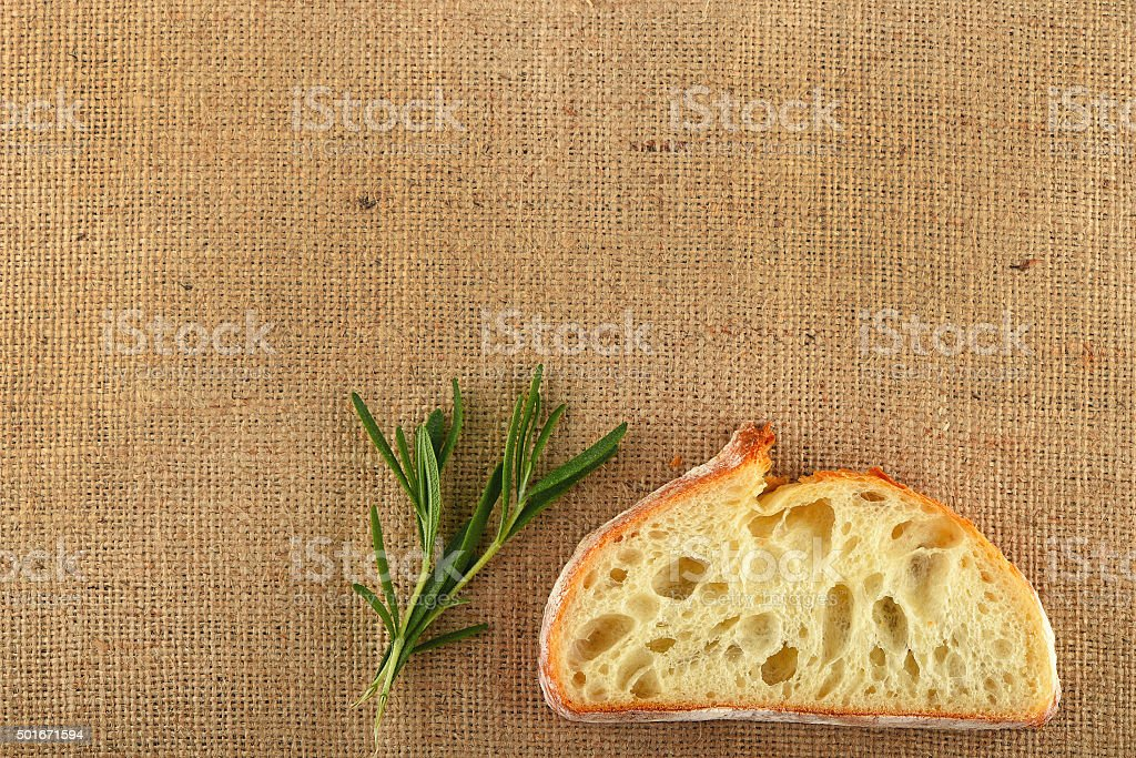 Canvas with rosemary leaves and slice of wheat bread royalty-free stock photo