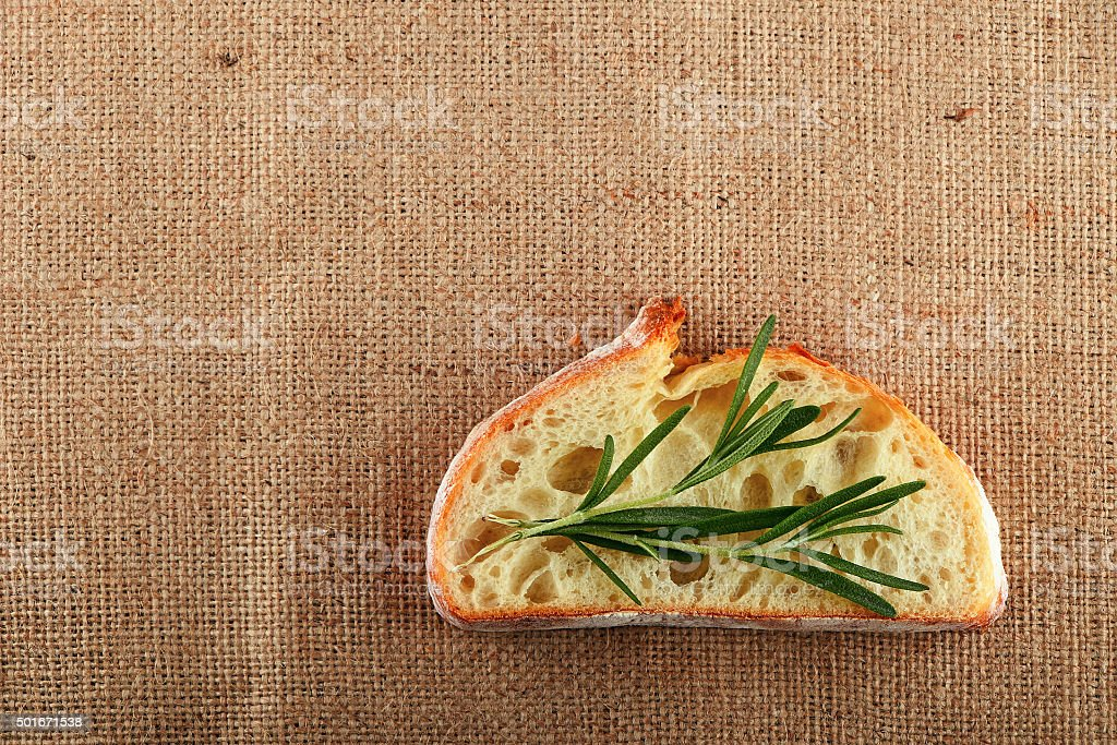 Canvas with rosemary leaves on slice of wheat bread royalty-free stock photo