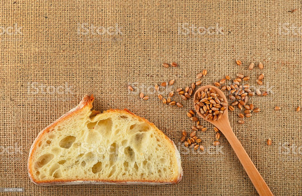 Canvas with slice of bread and ripe grains royalty-free stock photo