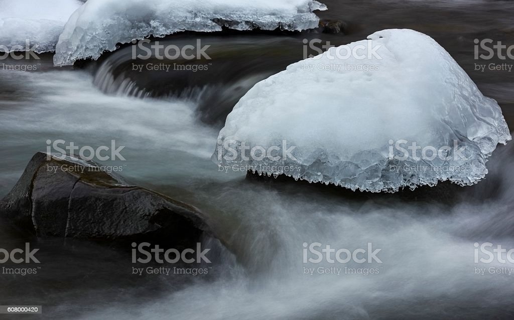 Cap of ice in frosted stream stock photo