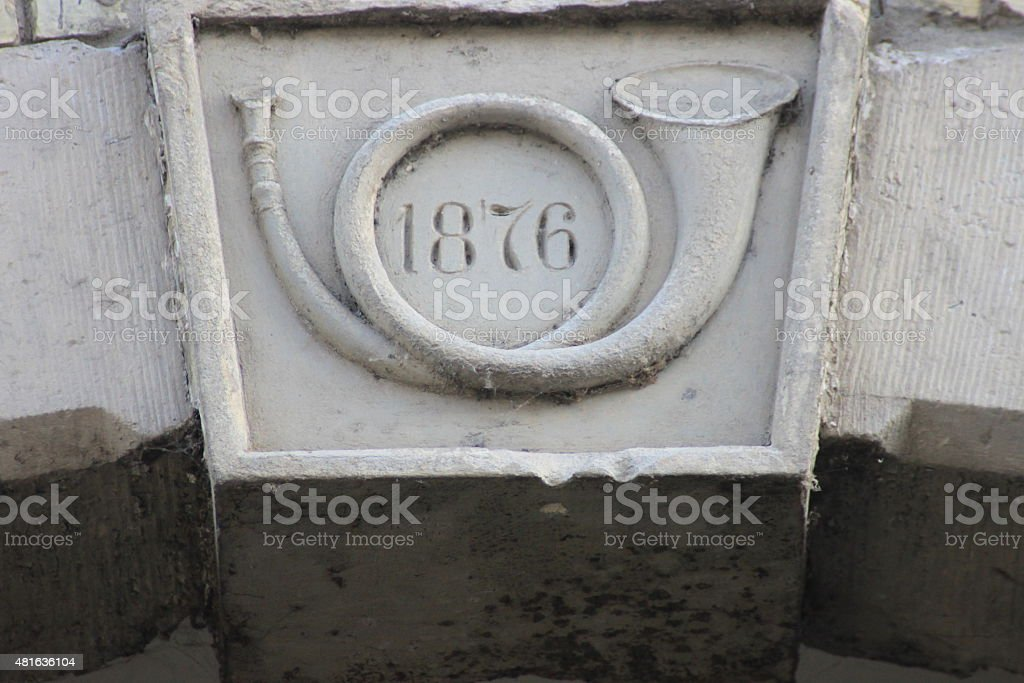 Cap stone from 1876 with post horn stock photo