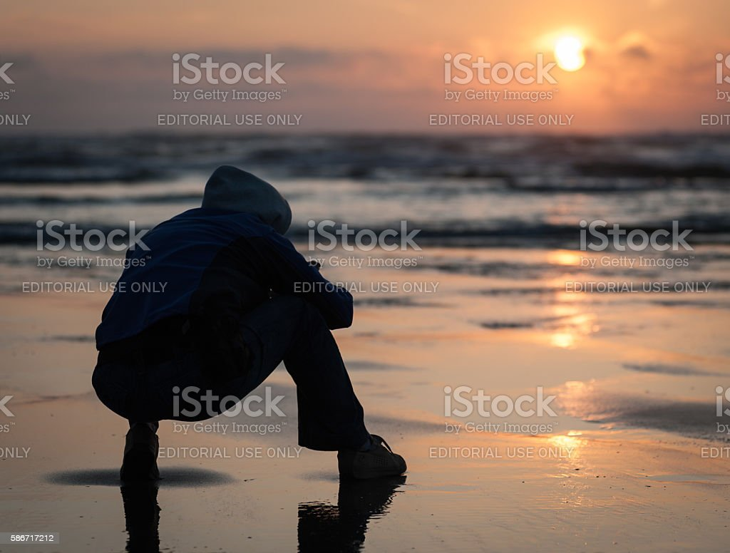 Cape Lookout sunset closeup with man silhouette sit stock photo