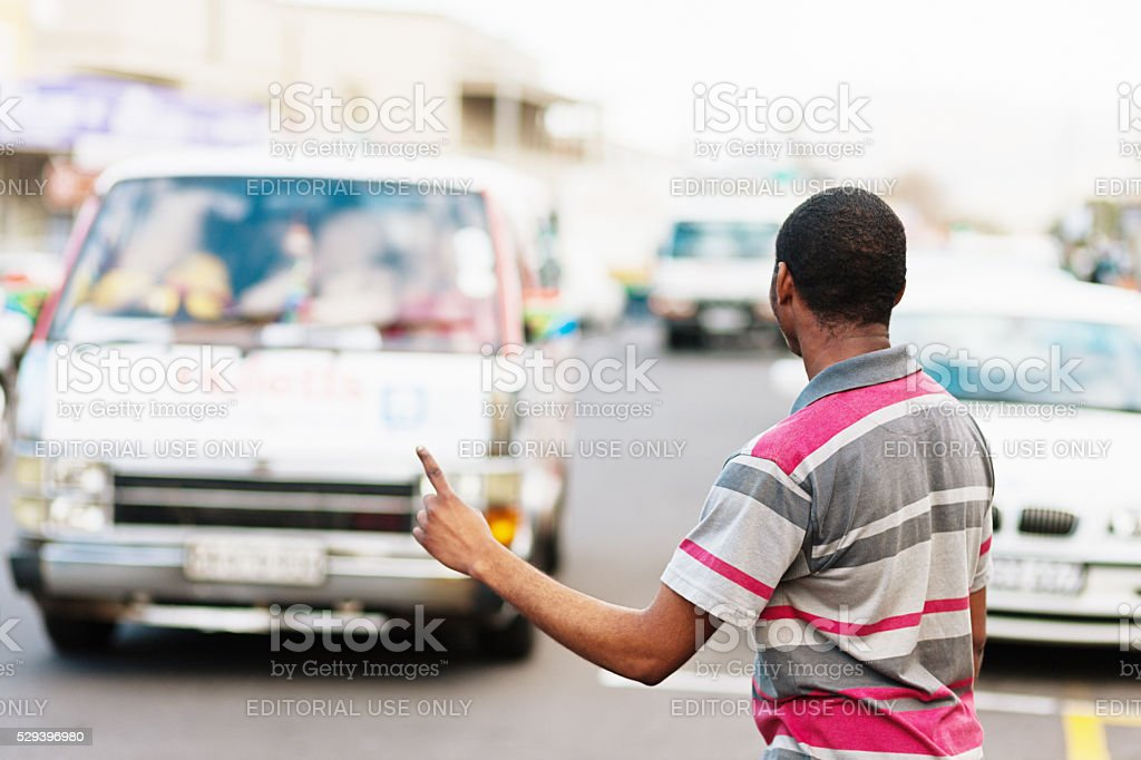 Cape Town man  showing required destination, hailing minibus taxi stock photo