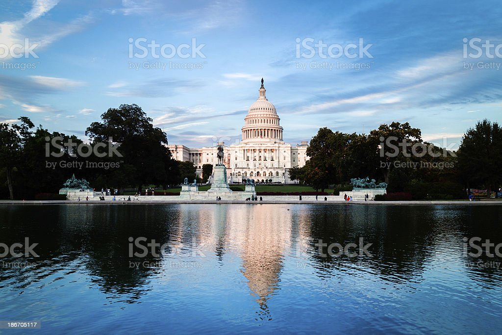 US Capitol building reflecting in water with blue sky stock photo