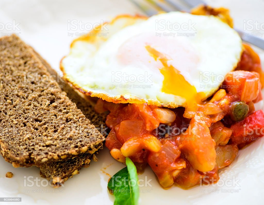 Caponata with Fried Egg and Rye Bread stock photo