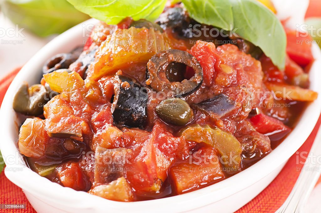 Caponata with olives in a white bowl royalty-free stock photo
