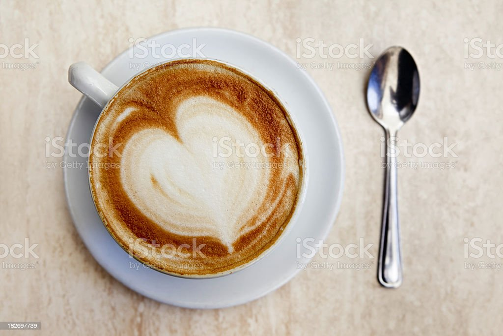 Cappuccino and spoon with heart-shaped foam royalty-free stock photo