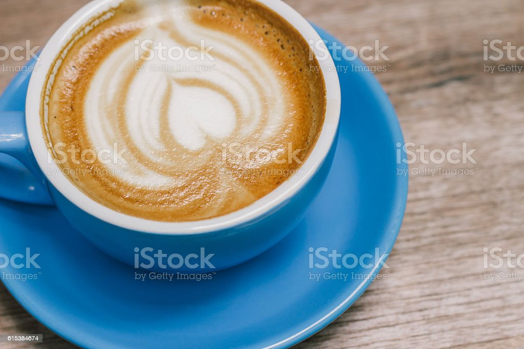 Cappuccino coffee art on wooden table stock photo