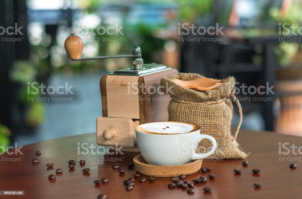 Cappuccino coffee cup on wood table with traditional coffee beans and grinder stock photo