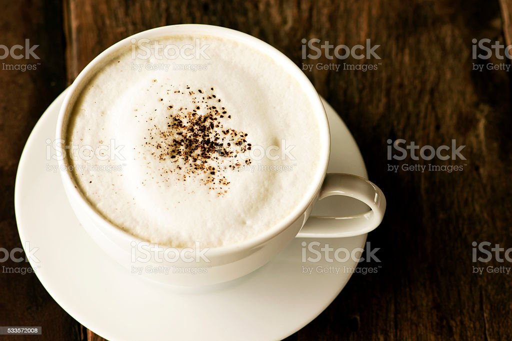 cappuccino coffee in white cup on wooden background stock photo