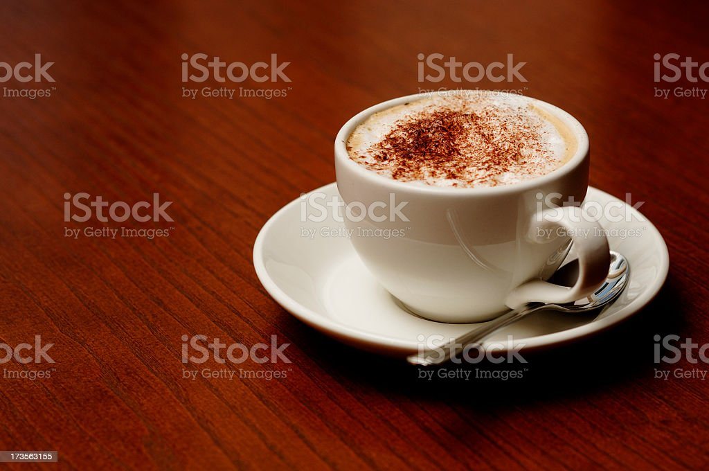 Cappuccino coffee on a wood table top with copyspace royalty-free stock photo
