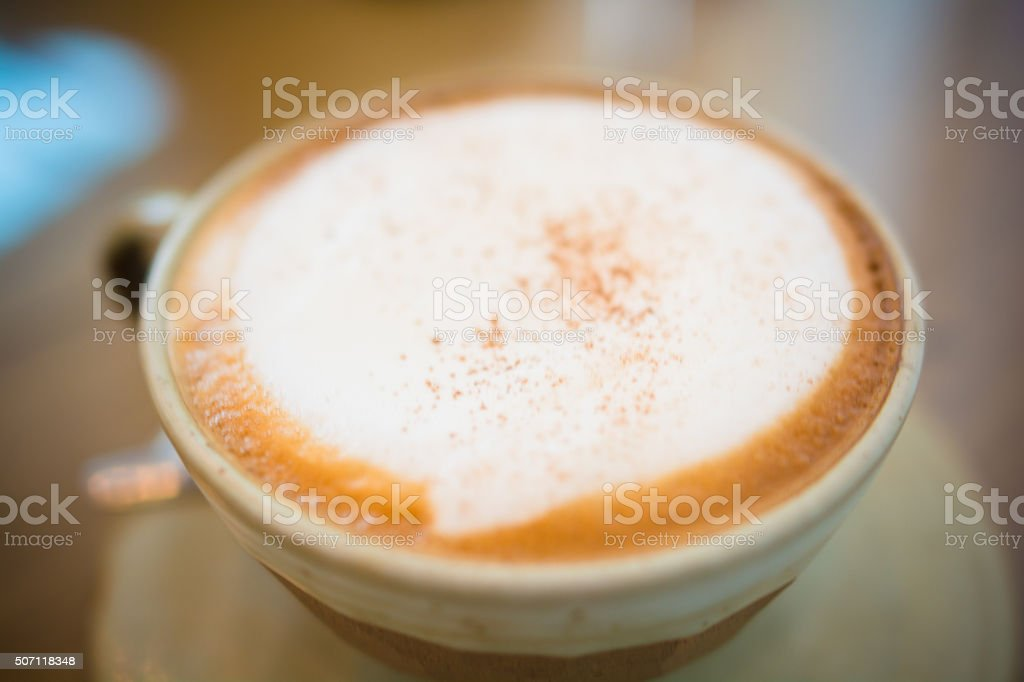 Cappuccino coffee on wood table focus at white foam stock photo