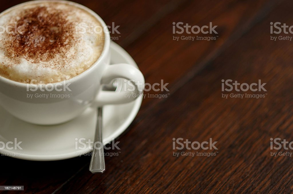 Cappuccino cup on dark wood table with copyspace royalty-free stock photo