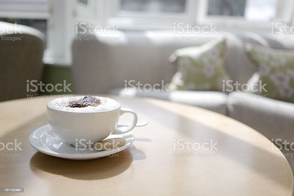 Cappuccino in a cup on a coffee table stock photo