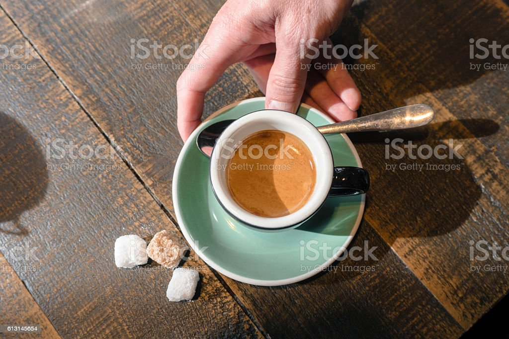 Cappuccino in a small black cup stock photo