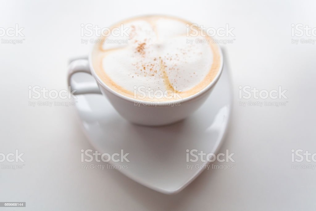 Cappuccino in a white cup on a white saucer. Still-life on a white background. stock photo