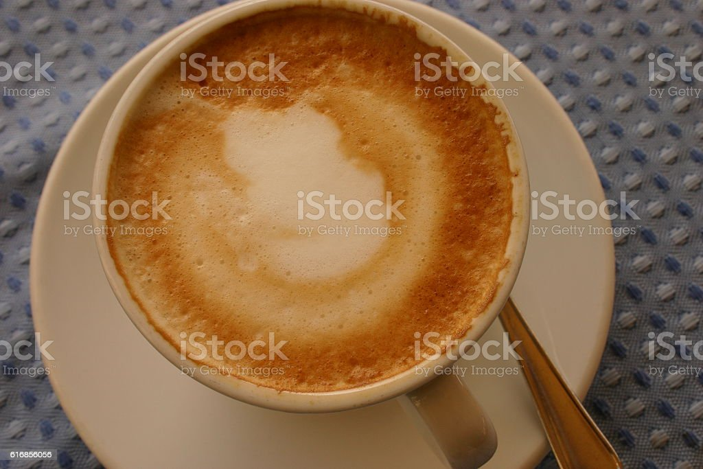 Cappuccino in white cup on blue table stock photo