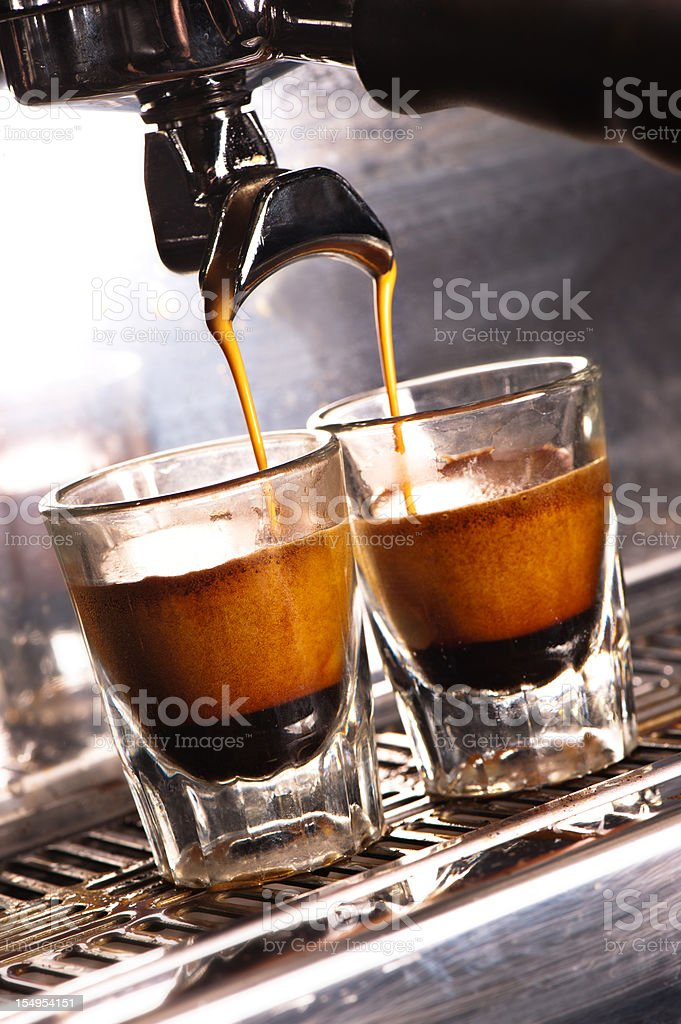 Cappuccino Machine pouring into two shot glasses. stock photo