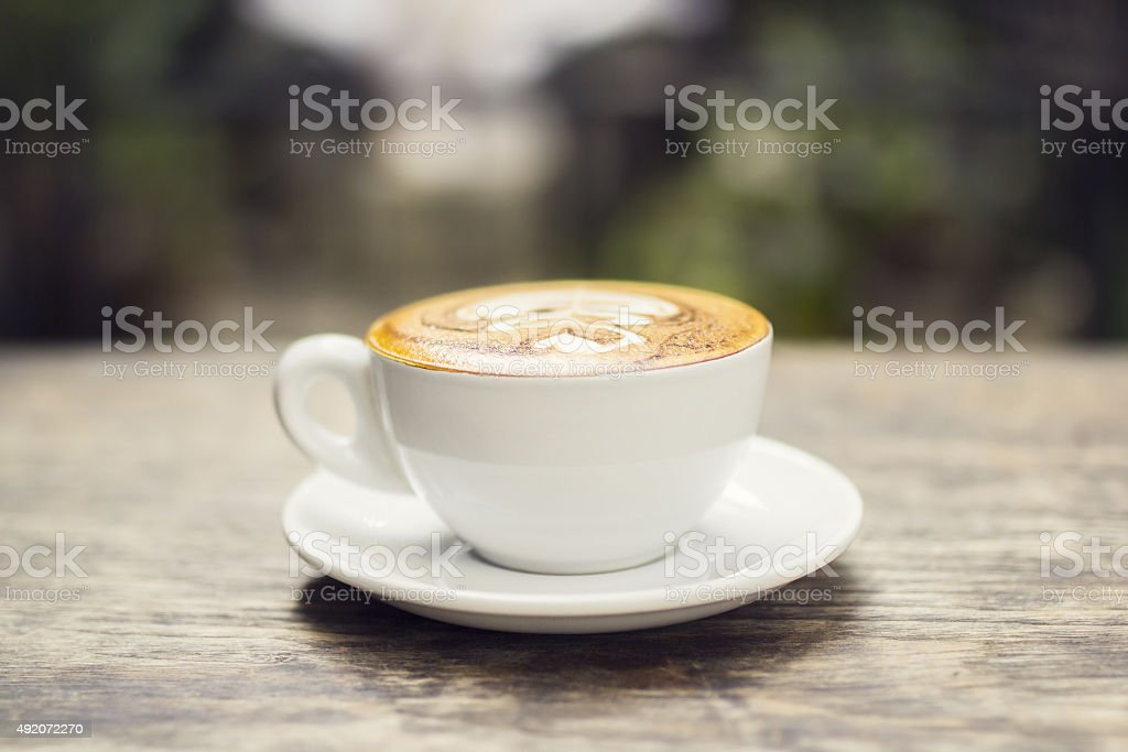 Cappuccino on a wooden table outside stock photo