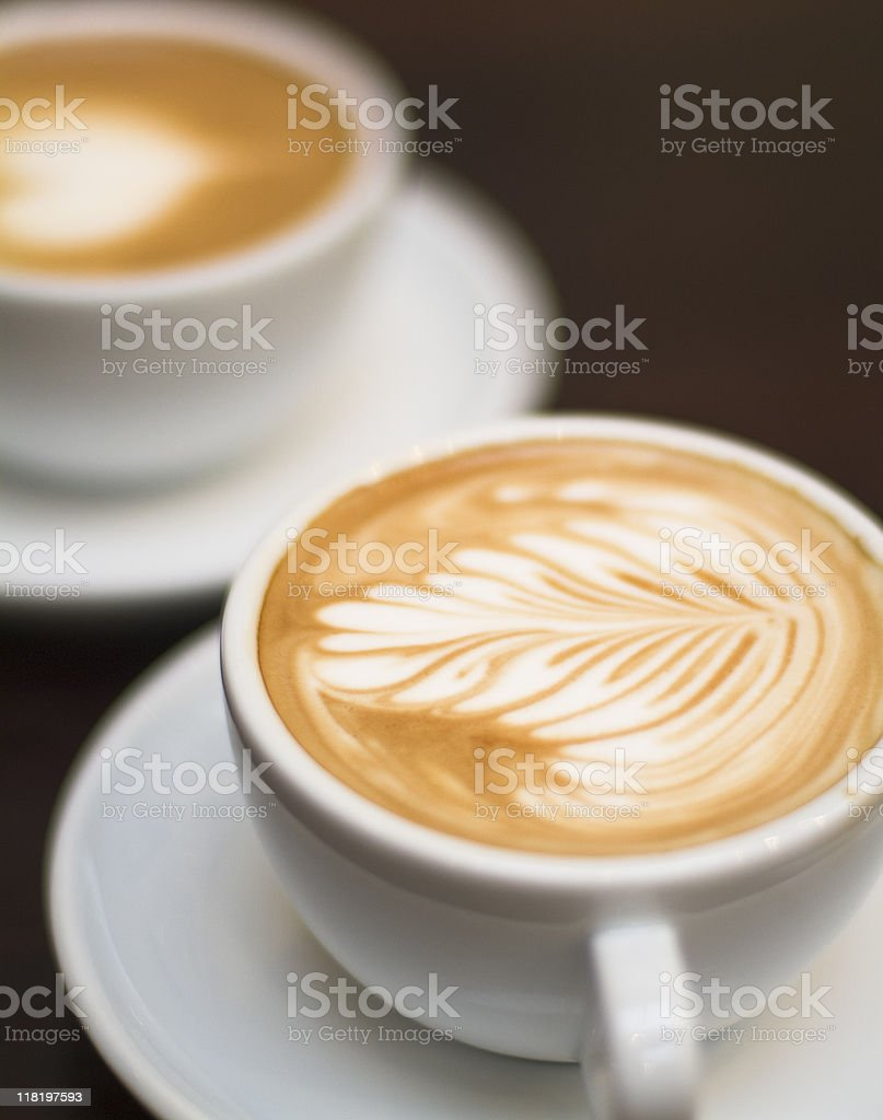 Cappuccino - One cup with decorated foam and bokeh background stock photo