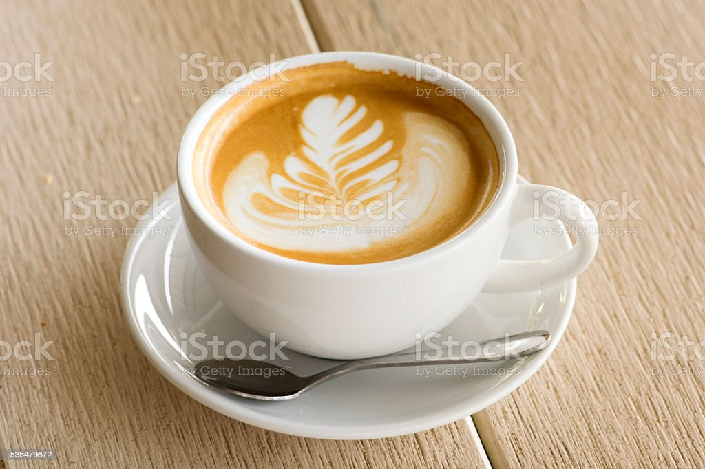 Cappuccino or latte coffee on wood background stock photo