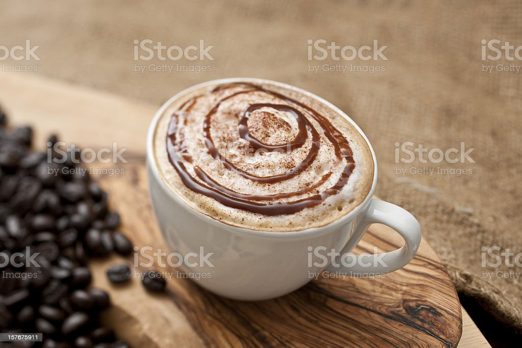 Cappuccino topped with swirls of chocolate sauce royalty-free stock photo