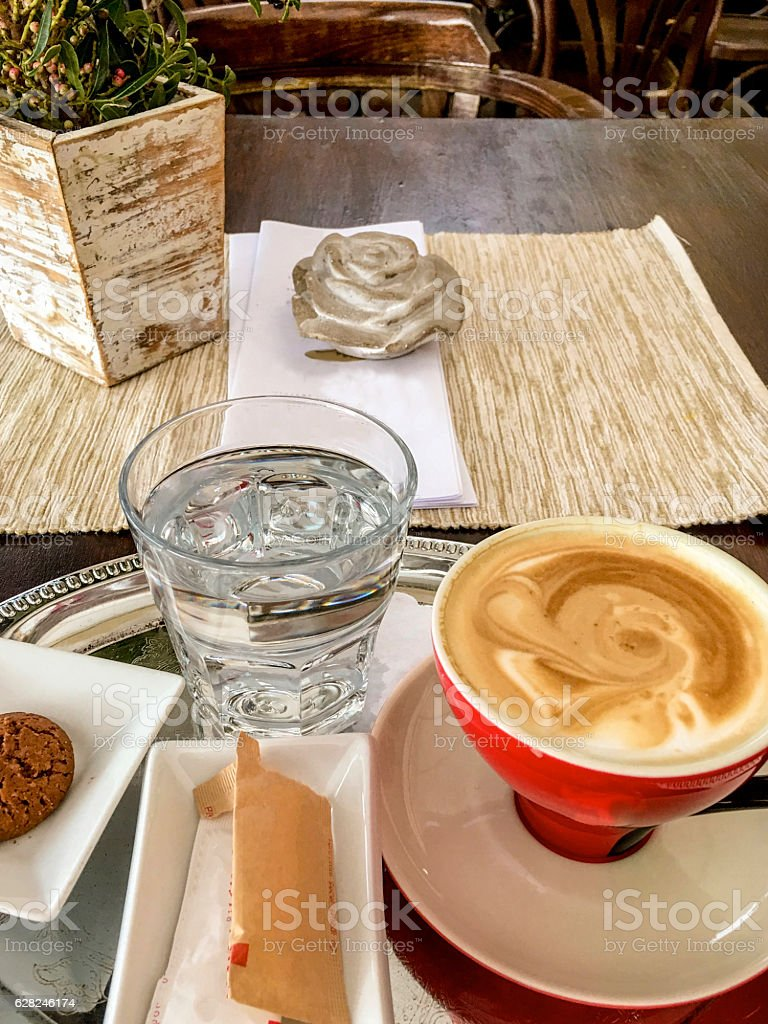 Cappuccino, water and cookie on a silver tray stock photo