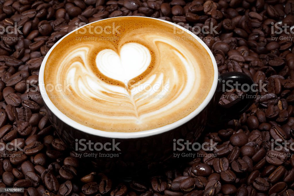 Cappuccino with a heart sitting in coffee beans royalty-free stock photo
