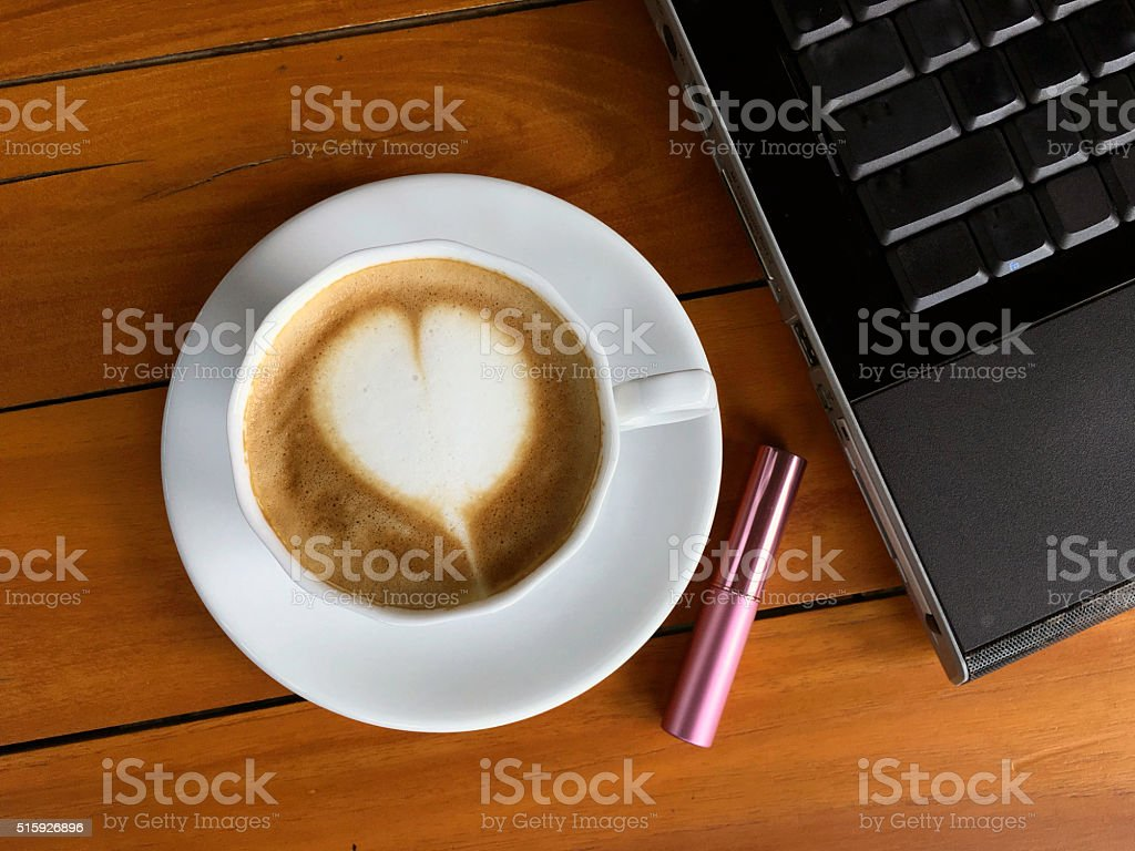 Cappucino with  lipstick and laptop on wood background royalty-free stock photo