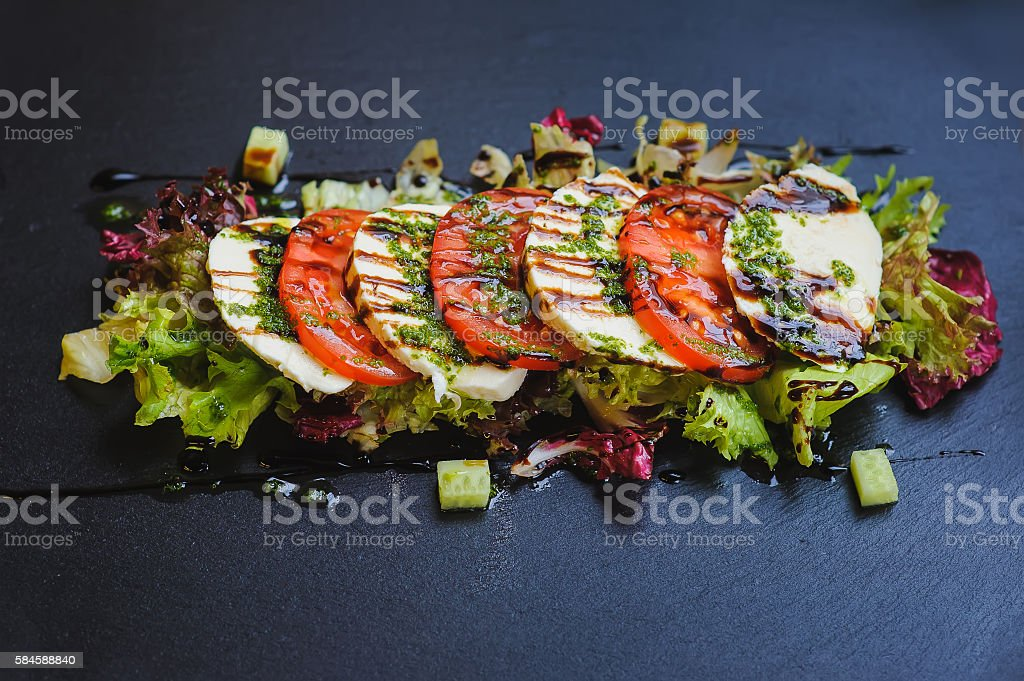 caprese - Italian salad on dark plate stock photo
