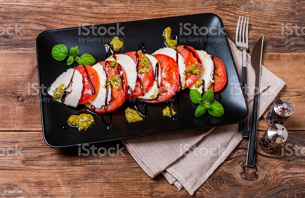 Caprese Salad on black plate stock photo