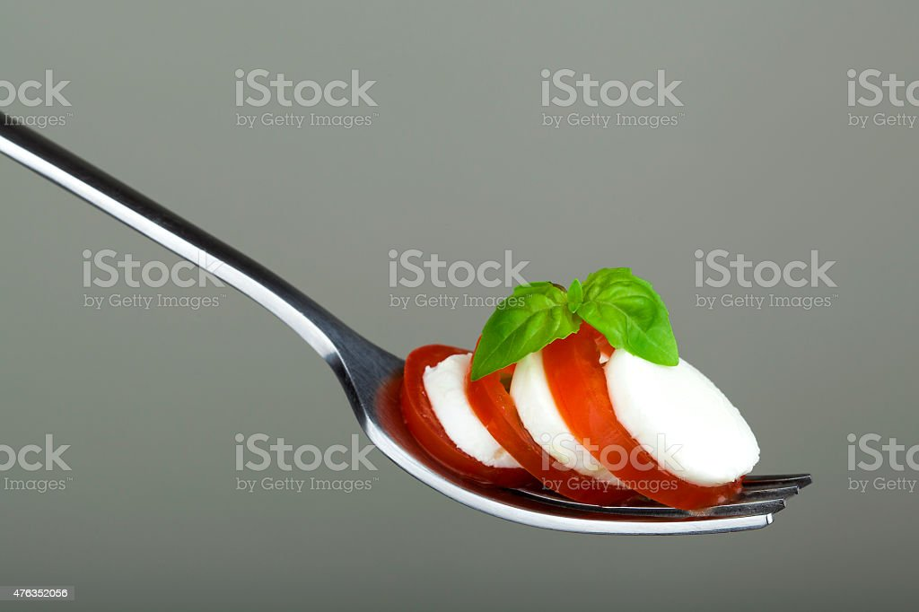Caprese salad on silver fork stock photo