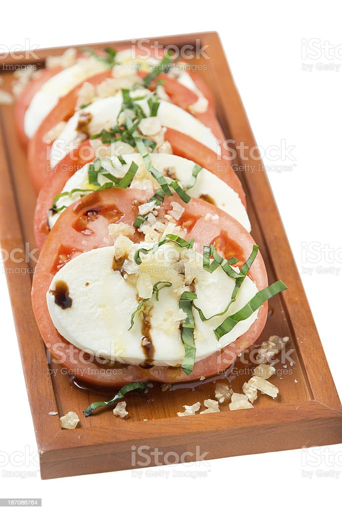 Caprese salad on wooden plate in white background royalty-free stock photo