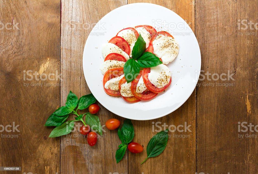 Caprese salad with mozzarella, tomato, basil on white plate. Top stock photo