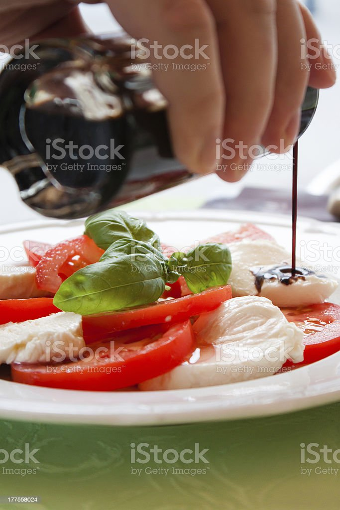 Caprese salad with pouring balsamico royalty-free stock photo