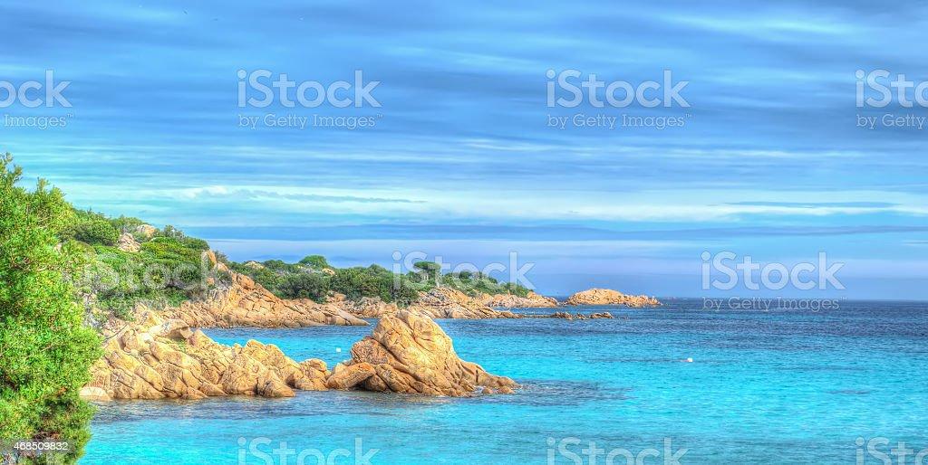 Capriccioli beach on a cloudy day stock photo