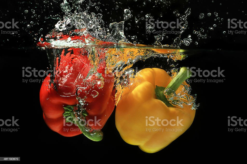 Fresh red and yellow bell pepper gets hit by a water stream on black...