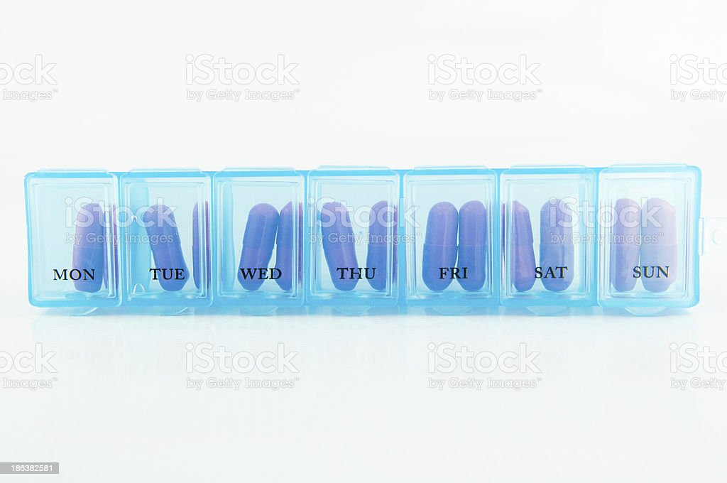 Capsule in blue daily pill box stock photo