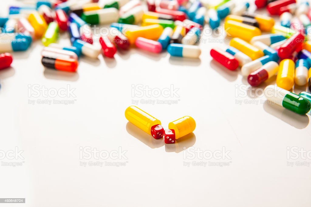 Capsule with miniature dice showing double ones. stock photo