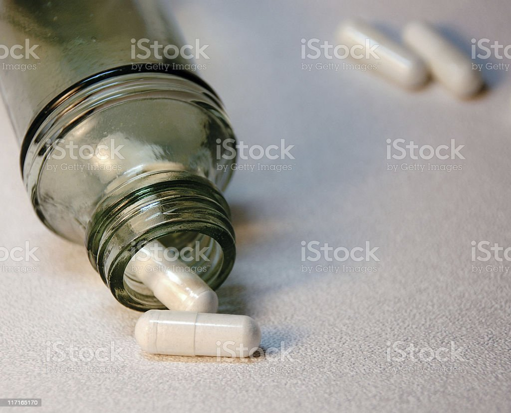 Capsules and glass bottle royalty-free stock photo