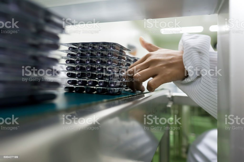 Capsules in packages being sorted by hand for quality control. stock photo