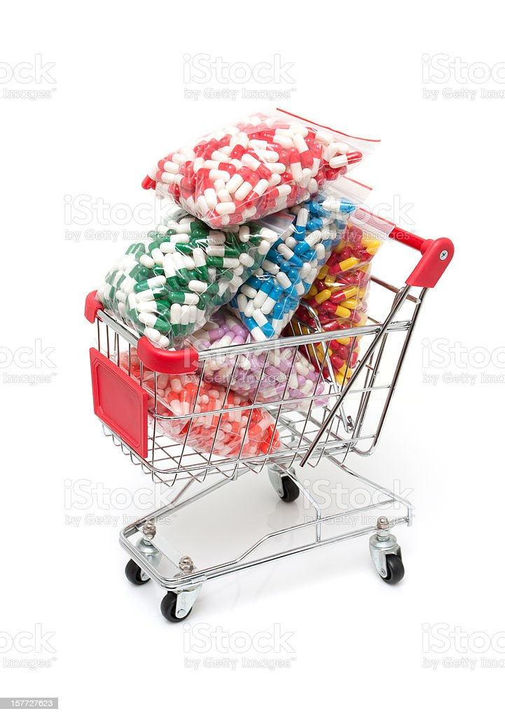 Capsules in shopping cart isolated on white background royalty-free stock photo